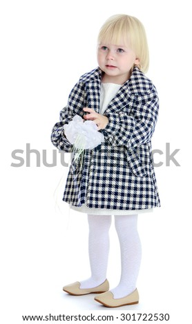 Pensive little blonde girl in autumn coat plaid and white stockings plays with her hands a bow he took off the head. See the girl is upset about something-Isolated on white background - stock photo