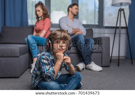 pensive little boy in headphones looking away while argued parents sitting on sofa