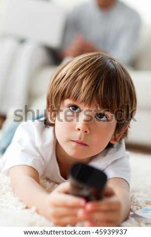 Pensive little boy watching TV lying on the floor in the living-room - stock photo