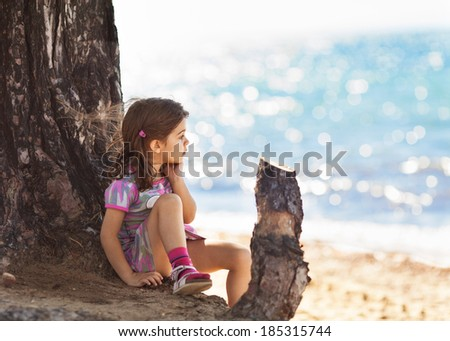 Pensive little girl portrait by the sea. - stock photo