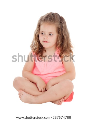 Pensive little girl sitting on the floor isolated on a white background - stock photo