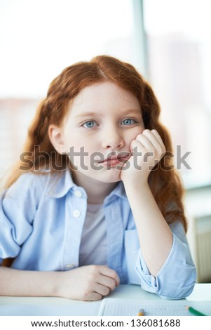 Pensive little girl touching her cheek and looking at camera - stock photo