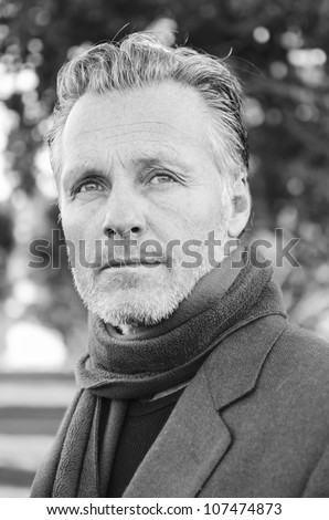 pensive looking mature man with beard wearing a scarf and jacket.