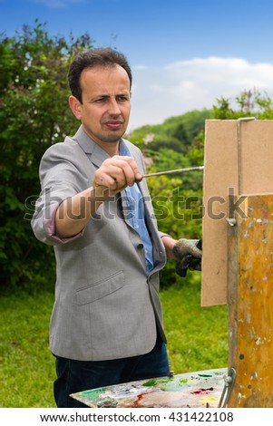 Pensive male painter panting his masterpiece wearing a glove and holding paintbrush in the open air with background of beautiful trees - stock photo