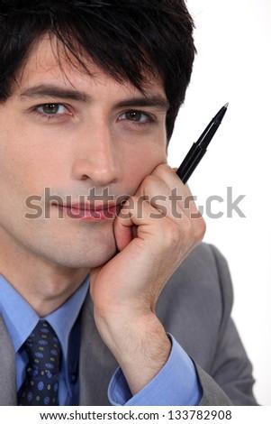Pensive man holding pen to mo face - stock photo