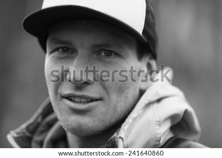 Pensive man in a trucker cap. Black and white close-up portrait - stock photo