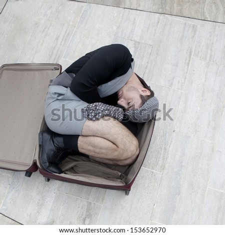 pensive man in check cap lying in broken trunk trying to escape - stock photo