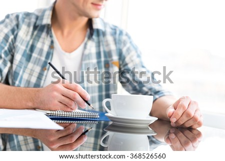 Pensive man in checkered shirt drawing in notepad and drinking coffee at the table - stock photo