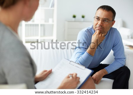 Pensive man in eyeglasses listening to psychologist - stock photo