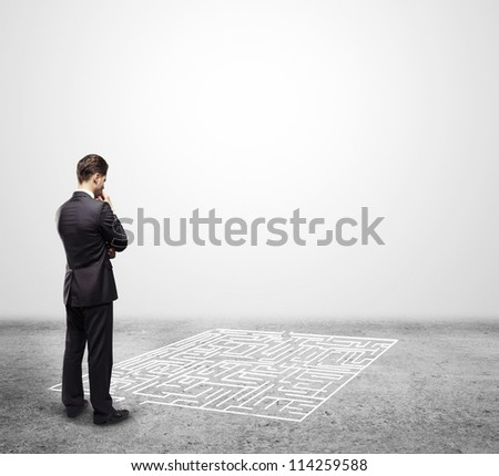 pensive man in front of labyrinth - stock photo