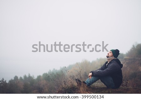 Pensive man is resting on a hill Man was plunged deep in thought and was lost in contemplation. He is enjoying the beautiful scenic view.  - stock photo
