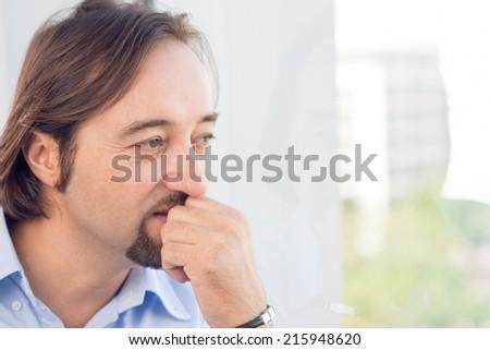 Pensive man looking through the window - stock photo