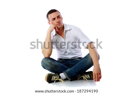 Pensive man sitting at the floor over white background - stock photo