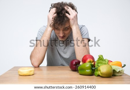 Pensive man sitting at the table with vegetables and donut - stock photo