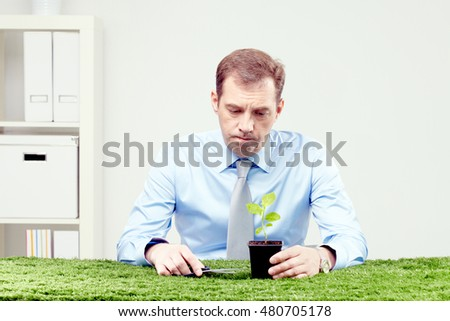 Pensive man sitting with plant and scissors