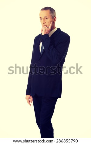 Pensive mature businessman touching chin. - stock photo