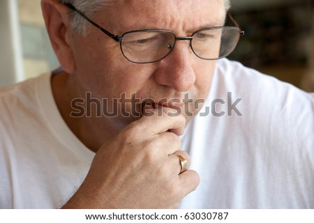 Pensive mature man closeup biting lip - stock photo