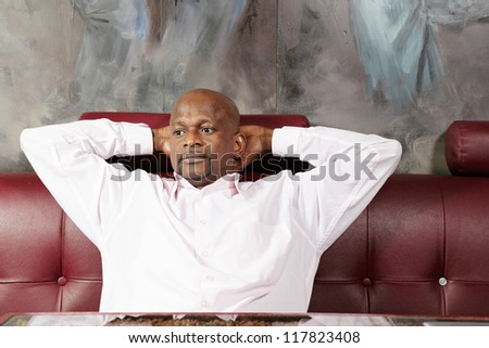 Pensive middle aged african man sitting on red leather sofa holding hands behind head - stock photo