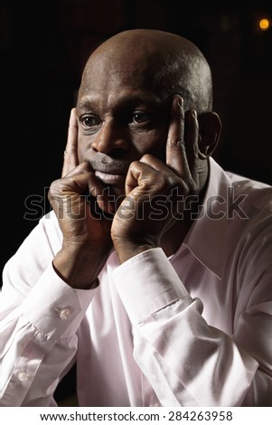 Pensive middle-aged bald guy in a pink shirt leaning on hands looking sideways  - stock photo