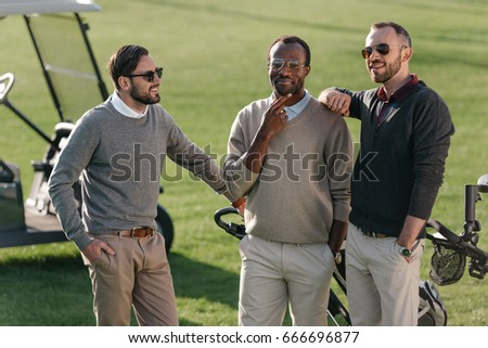 pensive multiethnic golf players standing on golf course