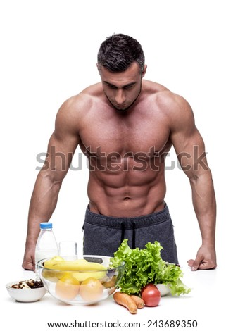 Pensive muscular man leaning on the table with healthy food - stock photo