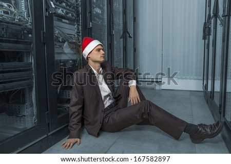 pensive network Engineer  in the server in Santa Claus lying on the floor on colorize background