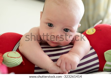 Pensive newborn lying on a crawling roll at home - stock photo