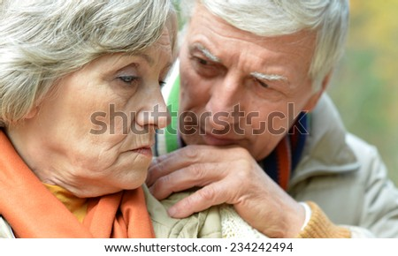 Pensive old couple posing at autumn park - stock photo
