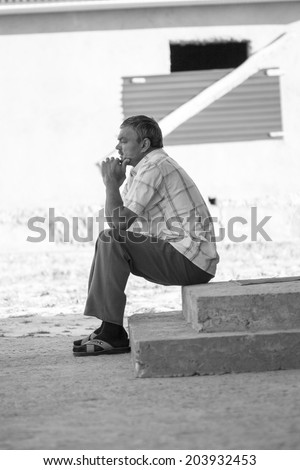 pensive old man sits quietly and thinks