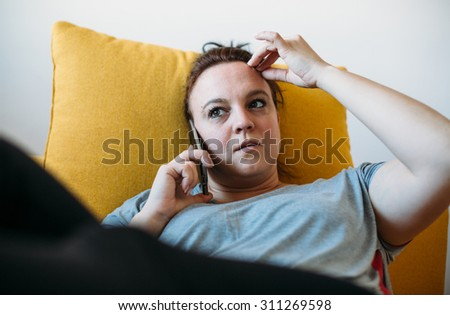 Pensive overweight woman talking on phone - stock photo
