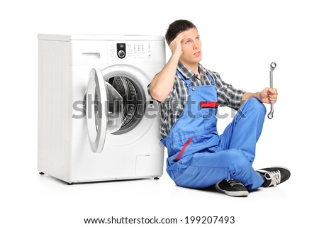 Pensive plumber fixing a washing machine isolated on white background