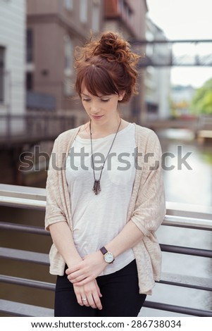 Pensive Pretty Girl in Casual Outfit, Leaning her Back Against the Railing on the Bridge While Looking Down Seriously. - stock photo