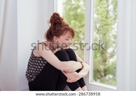 Pensive Pretty Girl Sitting Beside the Glass Window, Hugging her Knees with Eyes Closed. - stock photo