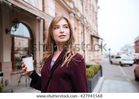 Pensive pretty young woman drinking coffee on the street of the city - stock photo