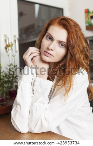 pensive redhead in the kitchen  - stock photo