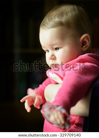 Pensive sad baby looking out the window into the street - stock photo