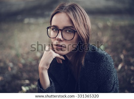 Pensive sad beautiful young woman in stylish sunglasses closeup on a city street - stock photo