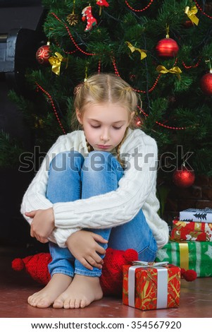 Pensive sad girl sits near a gifts and waiting New Year or Christmas. - stock photo