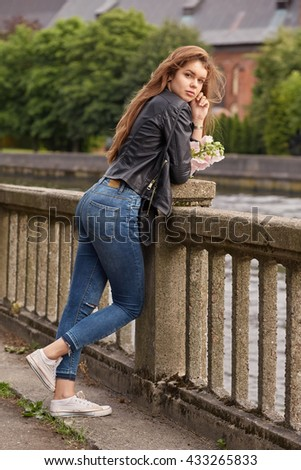 pensive sad woman with red hair near river
