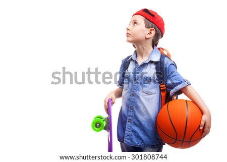 Pensive school boy holding a skateboard and a basketball on white background - stock photo