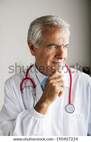 Pensive senior doctor with stethoscope - stock photo