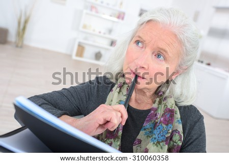 Pensive senior  with a notepad - stock photo