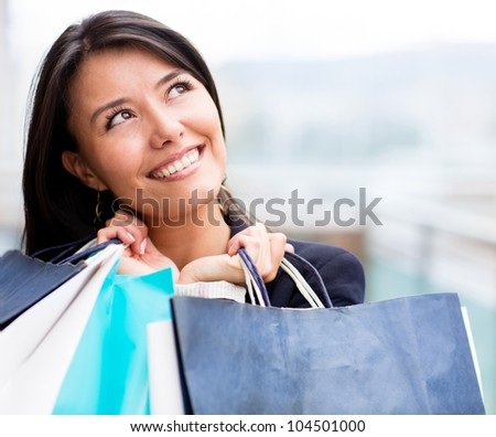 Pensive shopping woman holding bags and looking up