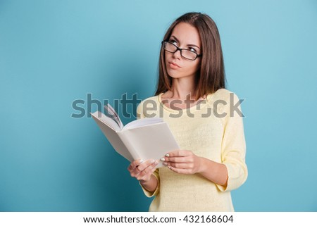 Pensive smart girl thinking about something and holding book isolated on the blue background - stock photo