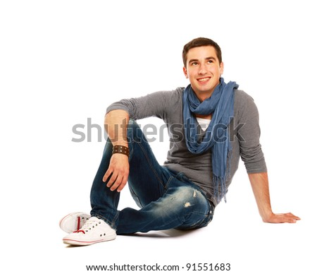 Pensive stylish young man sitting on floor and looking at copyspace , isolated on white background - stock photo