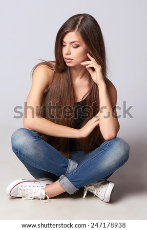 Pensive teen girl with beautiful hair sitting in full length on the studio floor looking to the side over gray background - stock photo