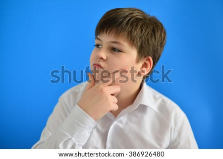 Pensive teenage boy on a blue background - stock photo