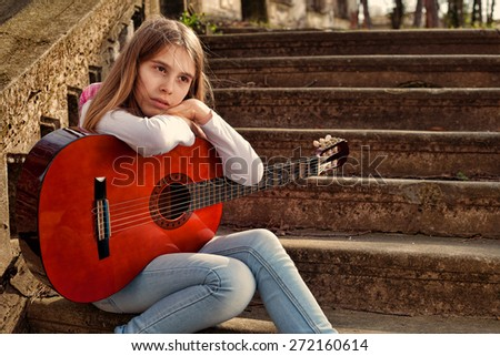 Pensive Teenage Girl Sitting on the Staircase and Holding a Guitar in Her Lap  - stock photo
