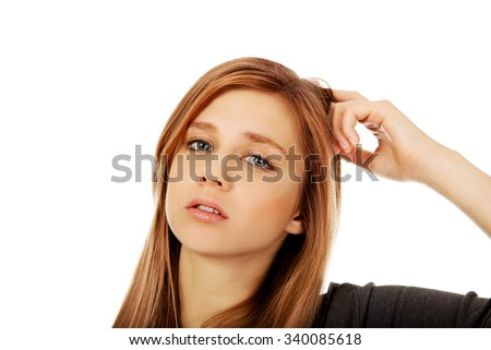 Pensive teenage woman scratching her head. - stock photo