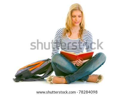 Pensive teengirl with schoolbag  sitting on floor and reading book isolated on white - stock photo